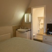 Standard single room bed, television and entrance to the ensuite.